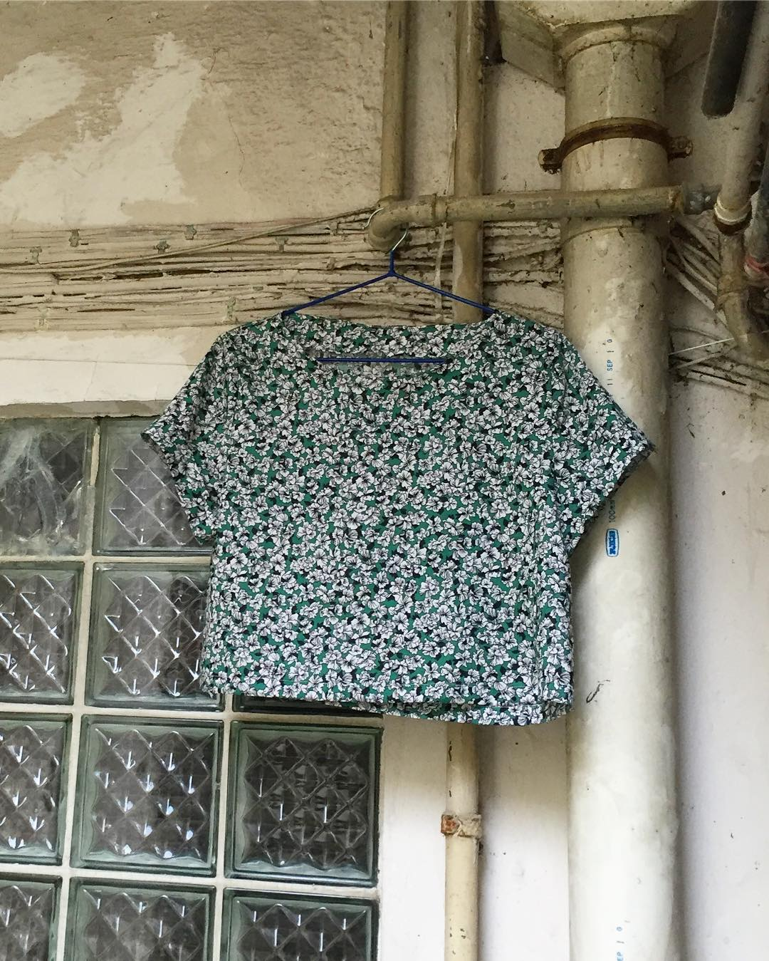 Inari Crop Tee hanging on a hanger